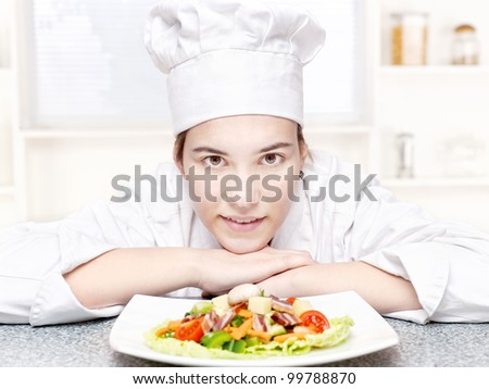 pretty young chef and hers plate of a delicious salad in kitchen - stock photo