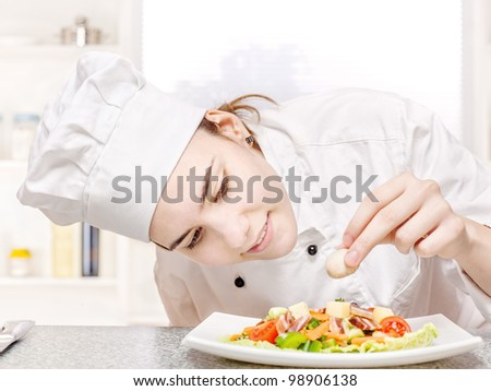 pretty young chef decorating delicious salad - stock photo