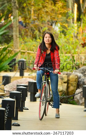Pretty young chinese woman in the park ride bicycle