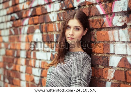 Pretty young city girl standing against an exterior brick wall sprayed with graffiti looking at the camera with a serious expression - stock photo