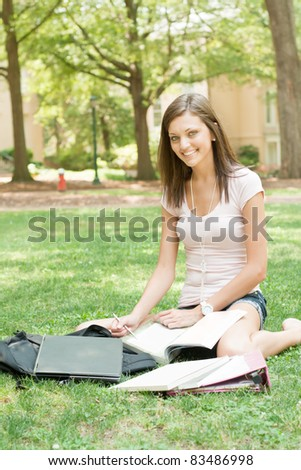 pretty young college or high school student with laptop and books - stock photo