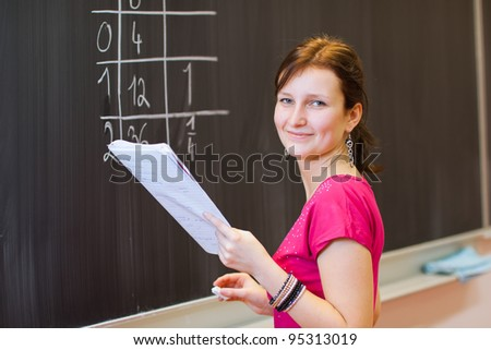 pretty young college student by the chalkboard/blackboard during a math class (color toned image)