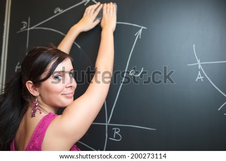 Pretty, young college student drawing on the chalkboard/blackboard during a math class (shallow DOF; color toned image) - stock photo