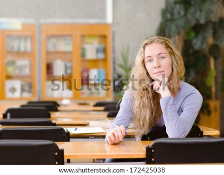 pretty young college student in a library. looking at camera