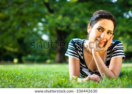 Pretty young college student thinking and writing while listening to music outdoors at campus - stock photo