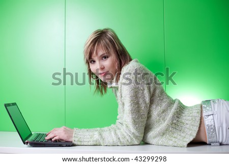 pretty young college student working on her laptop computer in front of a green wall (looking at you)