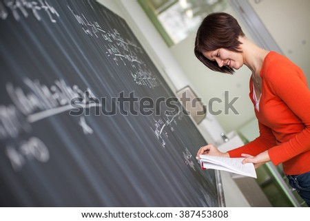 Pretty young college student/young teacher writing on the chalkboard/blackboard during a math class (color toned image) - stock photo