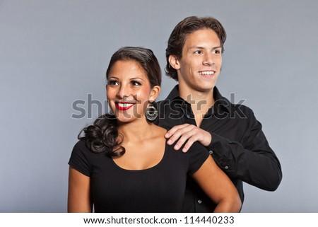 Pretty young couple dressed in black. Brother and sister. Good looking. Brown hair and eyes. Studio portrait isolated on grey background.