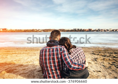 Pretty young couple sitting on the beach - stock photo
