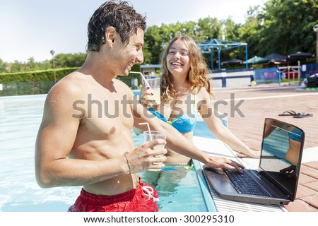 pretty young couple with laptop at swimming pool - stock photo