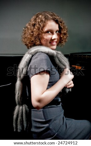 pretty young dark haired girl with curly hair sitting turned near piano in grey dress with fur scarf smiling isolated - stock photo