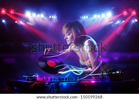 Pretty young disc jockey girl playing music with light beam effects on stage - stock photo