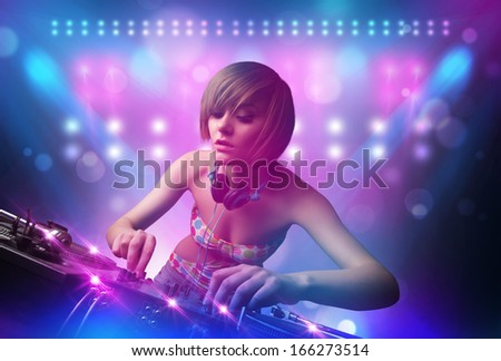 Pretty young disc jockey mixing music on turntables on stage with lights and stroboscopes - stock photo