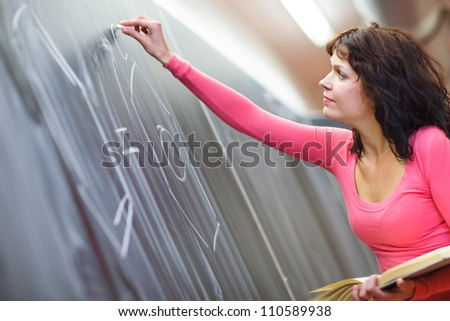 Pretty young elementary school/college teacher writing on the chalkboard/blackboard during a chemistry class (color toned image; shallow DOF) - stock photo