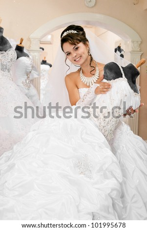 pretty young excited woman is choosing a wedding dress in the shop - stock photo