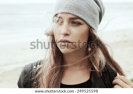 Pretty young fashion serious hipster woman posing outdoor in cold spring windy weather outdoor on the beach near the sea  - stock photo