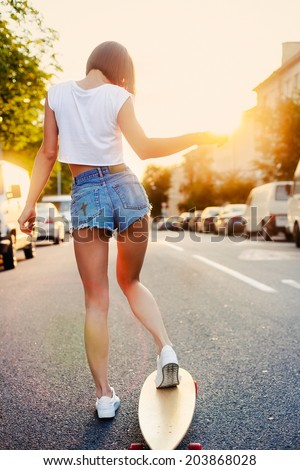 Pretty young fashion sexy swag girl riding wooden longboard on the road in evening summer time have fun and shows her nice back in jeans shorts hipster style  - stock photo
