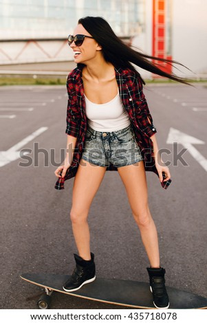 Pretty young fashion sexy swag girl riding wooden longboard on the road in evening summer time have fun and shows her nice back in jeans shorts hipster style