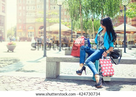 Pretty young fashion woman holding shopping bags and standing near shop window - stock photo