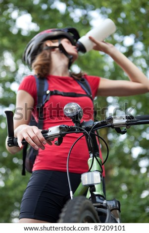 pretty young female biker outddors on her mountain bike (shallow DOF; selective focus)
