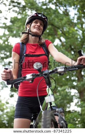 pretty young female biker outddors on her mountain bike (shallow DOF; selective focus) - stock photo