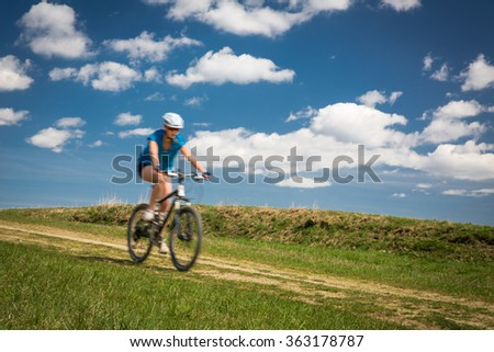 Pretty, young female biker outdoors on her mountain bike (motion blurred image)