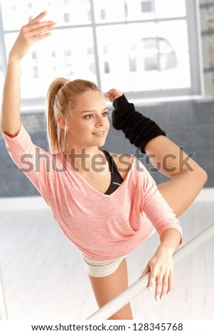Pretty young female dancer practicing by bar in gym. - stock photo