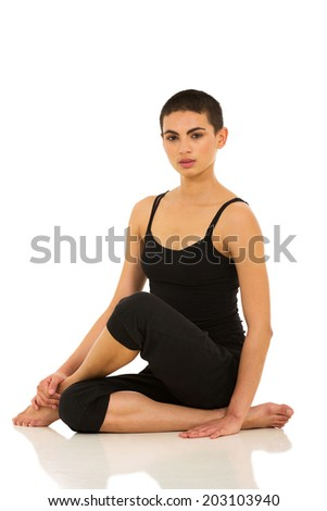 pretty young female dancer sitting on floor isolated on white background