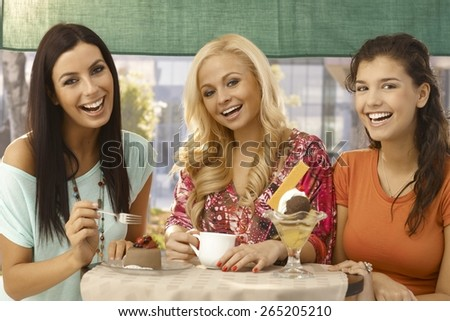 Pretty young female friends having cake and ice cream at outdoor cafe, smiling happy. - stock photo