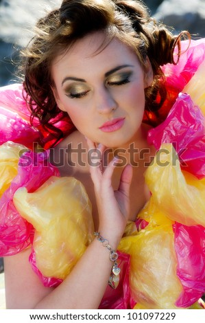 Pretty young female in plastic colourful dress