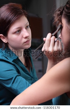 Pretty young female model having her makeup applied before her photoshoot - stock photo
