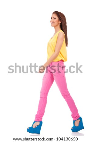 Pretty young female model in pink jeans walking on white background and smiling - Copyspace - stock photo