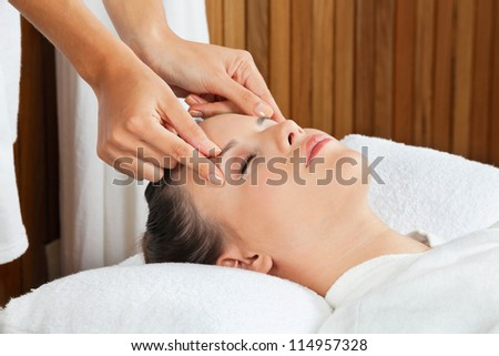 Pretty young female receiving a head massage at health spa - stock photo