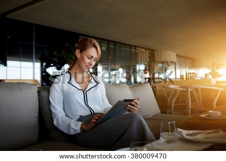Pretty young female search information on digital tablet while waiting for her friend in modern cafe interior,elegant businesswoman using touch pad while reading feminine website of fashion and health - stock photo