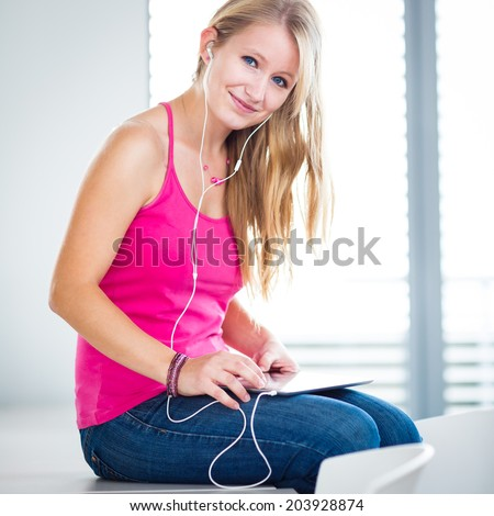 Pretty, young female student listening to music on her tablet computer (color toned image) - stock photo