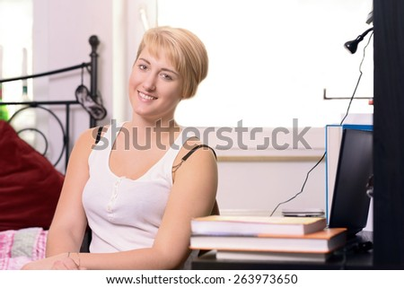 Pretty young female student sitting in her bedroom with her text books studying and pausing to look at the camera with a friendly warm smile - stock photo