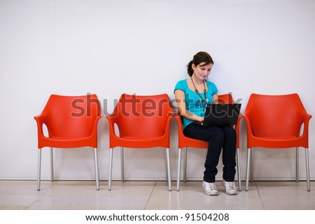 Pretty young female student with laptop on college/university campus - stock photo