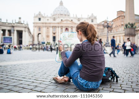 Pretty young female tourist studying a map at St. Peter's square in the Vatican City in Rome - stock photo