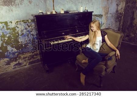 pretty young girl at piano retro vintage interior - stock photo