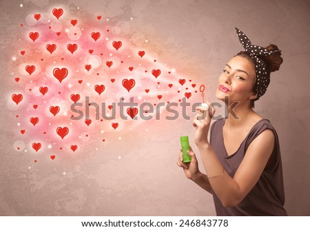 Pretty young girl blowing valentine red heart symbols  - stock photo