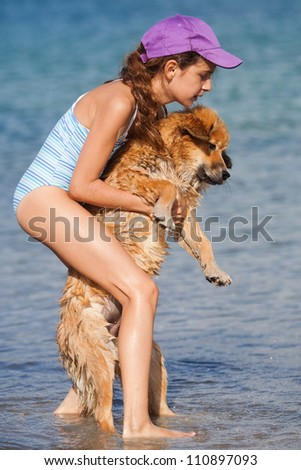pretty young girl carries an Elo puppy in the sea water