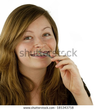 Pretty young girl demonstrating small specialized toothbrush for cleaning a bracket system isolated on white background
