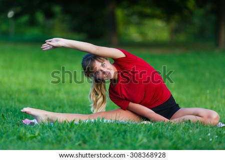 Pretty young girl doing split exercises outdoor