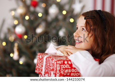 Pretty young girl dreaming of Christmas as she rests her chin on top of a decorative gift in colorful red wrapping with a sparkling Christmas tree behind - stock photo
