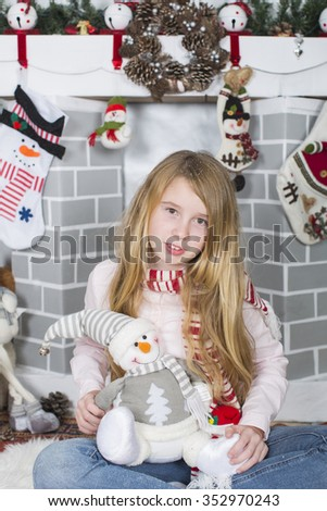 Pretty young girl dreaming of Christmas on top of a decorative gift and with a Christmas tree behind