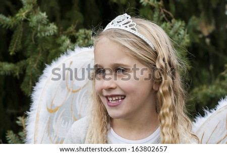 Pretty, young girl dressed as an angel next to a fir tree outside