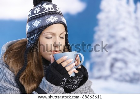 Pretty young girl dressed up warm for skiing wearing cap and gloves drinking hot drink eyes closed front of winter landscape .? - stock photo