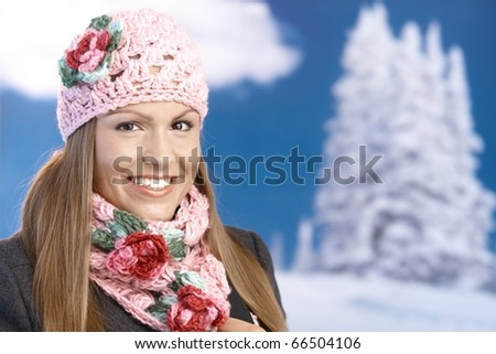 Pretty young girl dressed up warm in coat, cap and scarf, smiling front of winter landscape .? - stock photo