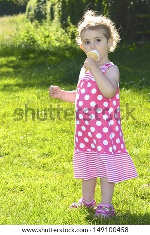 Pretty young girl eating ice cream. She is wearing a pink and white dress, with the sun behind her (backlit). She has blonde curly hair and is looking towards the camera. Full length shot.  - stock photo