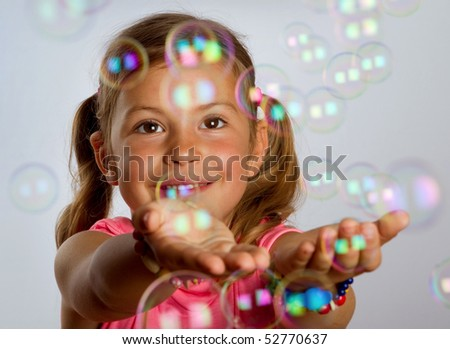 Pretty young girl enjoys catching bubbles that are floating in the air